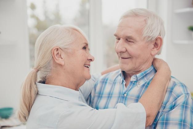 Twee mooie oude mensen vieren feest, langzaam dansen in flat binnenshuis