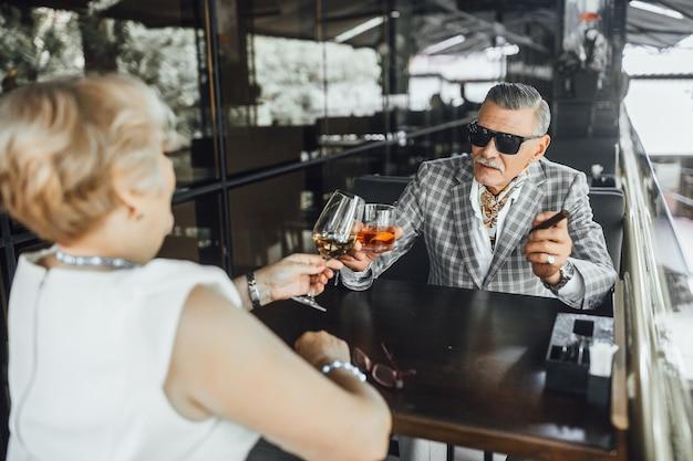 Twee mooie oudere mensen zitten in het moderne café en testen wijn
