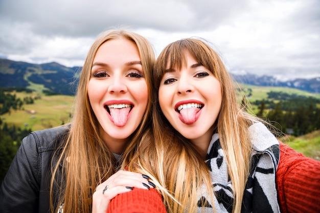 Twee mooie reizigersmeisjes die grappige selfie maken bij bergen. lange tongen laten zien, gek worden.