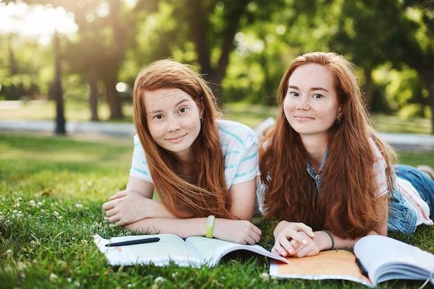 Twee mooie roodharige vrouwelijke studenten liggend op gras in park tijdens zomerdag, essays schrijven of project maken, glimlachend. levensstijl en vriendschapsconcept