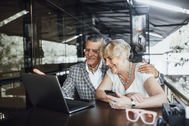 Twee mooie seniorenouders chating met hun kinderen in laptop