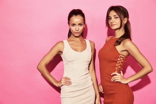 Twee mooie sexy glimlachende damesmodellen dragen een stijlvolle design trend katoenen kleding, casual zomerstijl voor een date meeting walk party. donkerbruine hete onderneemstervrouwen die op roze muur stellen
