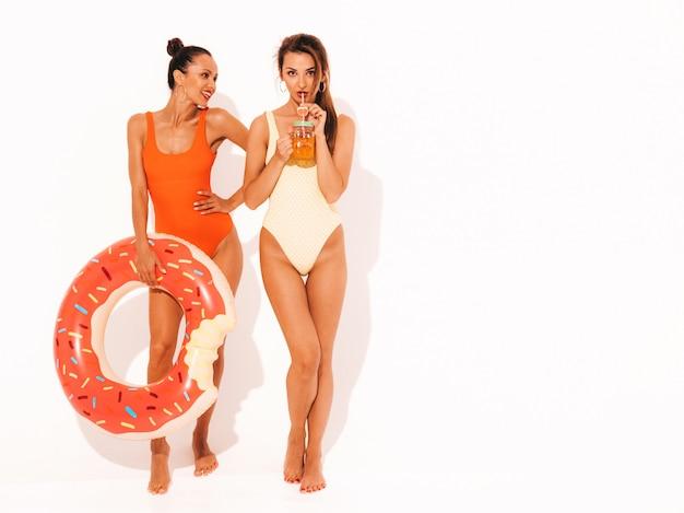 Twee mooie sexy glimlachende vrouwen in badpakken van de zomer de kleurrijke badmode. meisjes geïsoleerd. grappige modellen die verse cocktail smoozy drinken met opblaasbaar matras met donutlila