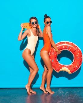 Twee mooie sexy glimlachende vrouwen in badpakken van de zomer de kleurrijke badmode. meisjes in zonnebril. positieve modellen met plezier met kleurrijke cent skateboard. met donut lilo opblaasbaar matras