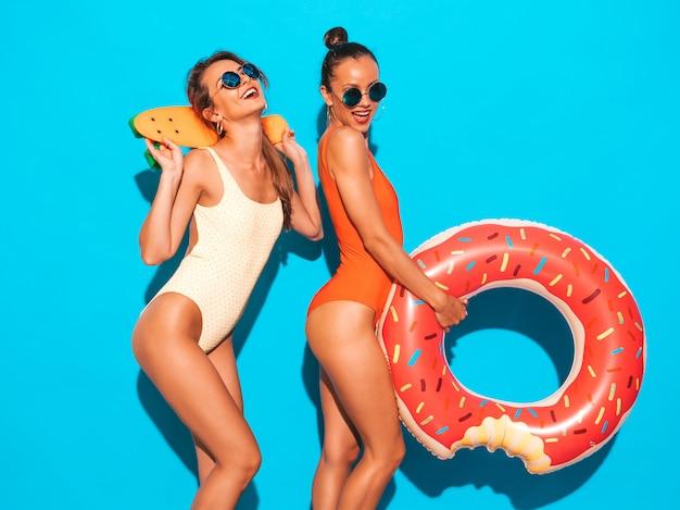 Twee mooie sexy glimlachende vrouwen in badpakken van de zomer de kleurrijke badmode. meisjes in zonnebril. positieve modellen met plezier met kleurrijke penny skateboards. met donut lilo opblaasbaar matras