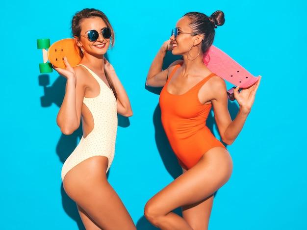 Twee mooie sexy glimlachende vrouwen in badpakken van de zomer de kleurrijke badmode. trendy meisjes in zonnebril. positieve modellen met plezier met kleurrijke penny skateboards. geïsoleerd