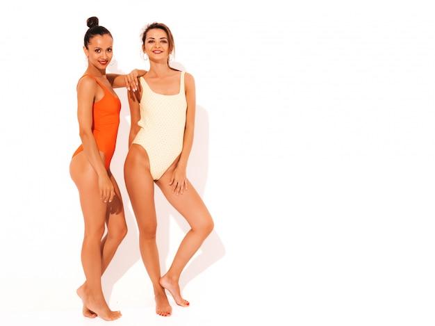 Twee mooie sexy glimlachende vrouwen in de zomer kleurrijke rode en gele badmode badpakken. trendy hete modellen met plezier. meisjes geïsoleerd