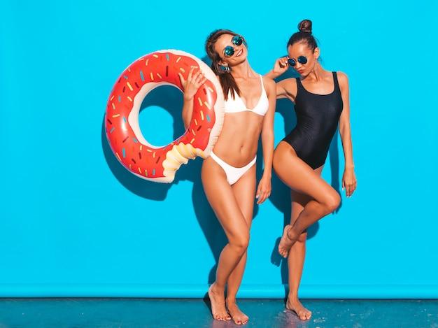 Twee mooie sexy glimlachende vrouwen in de zomer witte en zwarte badkleding badpakken. meisjes in zonnebril. positieve modellen die plezier hebben met de opblaasbare matras van donutlila. geïsoleerd op blauwe muur
