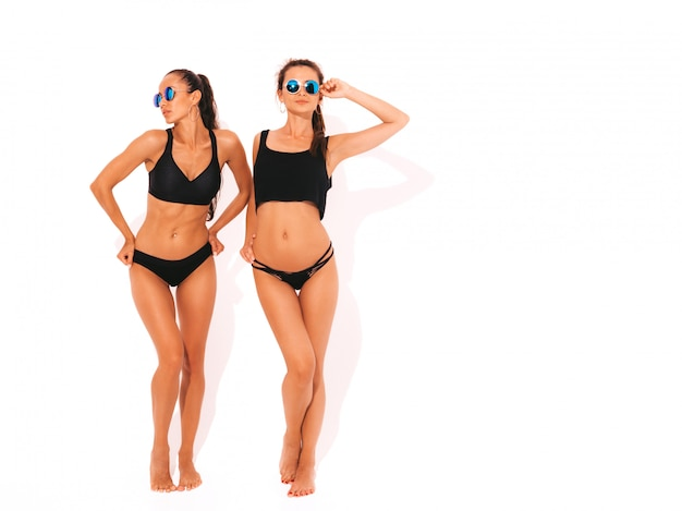 Twee mooie sexy glimlachende vrouwen in zwarte lingerie. trendy hete modellen met plezier. meisjes geïsoleerd in zonnebril. volledige lengte