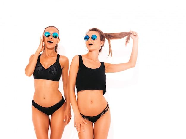 Twee mooie sexy glimlachende vrouwen in zwarte lingerie. trendy hete modellen met plezier. meisjes geïsoleerd in zonnebril