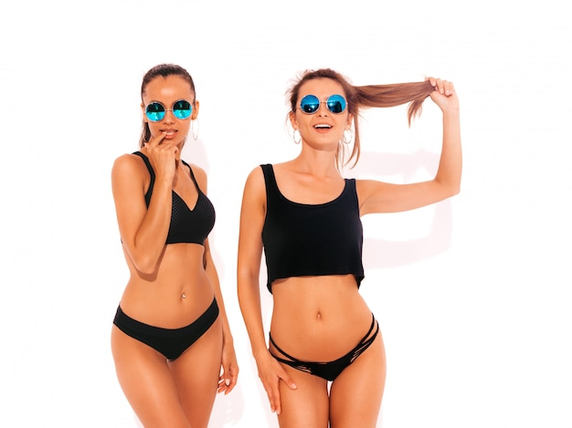 Twee mooie sexy glimlachende vrouwen in zwarte lingerie. trendy hete modellen met plezier. meisjes geïsoleerd