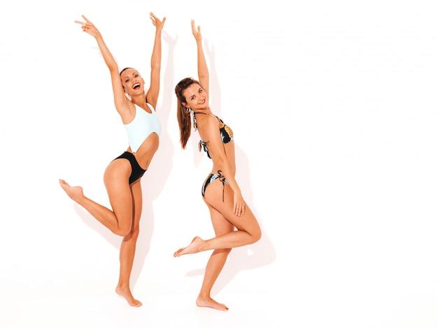 Twee mooie sexy glimlachende vrouwen in zwemmende lingerie. trendy hete modellen met plezier. geïsoleerde meisjes. opheffende handen, volledige lengte