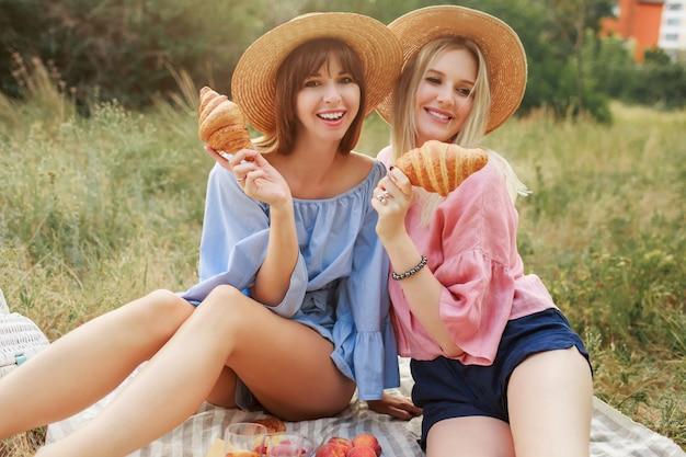Twee mooie speelse vrouwen poseren op gazon in zomerpark, genieten van lekker eten, croissants en wijn.