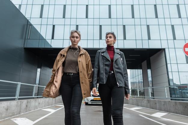Twee mooie stijlvolle jonge vrouwen in een leren jas met een trui en zwarte modieuze jeans lopen in de buurt van een modern glazen gebouw in de stad