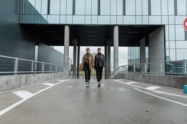 Twee mooie stijlvolle jonge vrouwen in modieuze herfstkleren lopen langs de weg in de moderne stad