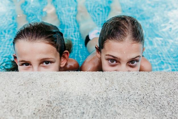 Twee mooie tienermeisjes die in een pool drijven en de camera bekijken. plezier en zomer levensstijl