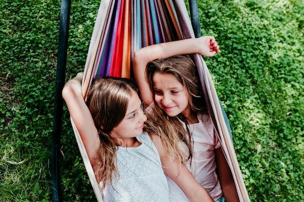 Twee mooie tienermeisjes die op kleurrijke hangmat bij de tuin liggen