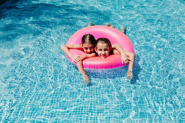 Twee mooie tienermeisjes die op roze donuts in een pool drijven. glimlachend. plezier en zomer levensstijl