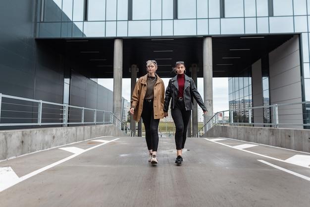Twee mooie tienermeisjes in modieuze leren outfit met een jas en zwarte spijkerbroek lopen in de stad