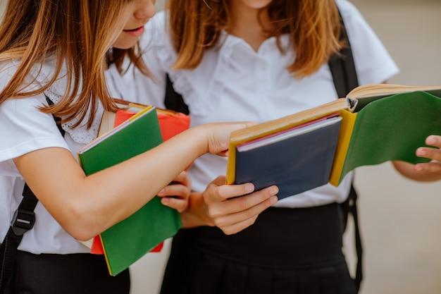Twee mooie tienermeisjes in zwart-wit schooluniform lezen een boek buiten. de nadruk is bij het linkermeisje en haar hand.