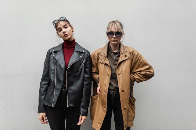 Twee mooie tienermodelmeisjes in modieuze leren jas met gebreide trui en jeans met zonnebril poseren in de buurt van de grijze muur op straat