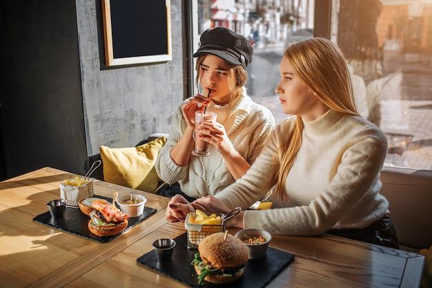 Twee mooie tieners zitten aan tafel in café en kijken naar links. drink eerst een cocktail. tweede zit naast vriend. ze zijn aat venster. zon schijnt buiten.