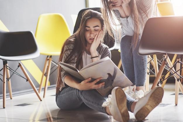 Twee mooie tweelingmeisjes brengen 's ochtends tijd door met het lezen van een boek in de bibliotheek. zusters ontspannen in een café en samen plezier maken
