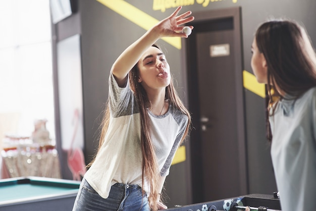 Twee mooie tweelingvrouwen spelen tafelvoetbal en hebben plezier. een van de zussen houdt een speelgoedbal in zijn hand en laat de tong zien