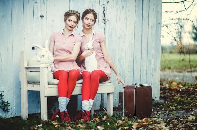 Twee mooie tweelingzusjes zitten met konijnen