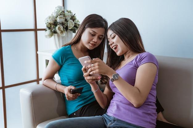 Twee mooie tweelingzusvrouwen die thuis de mobiele telefoon bekijken