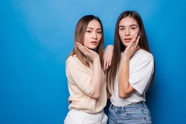 Twee mooie verrast schreeuwen met hun handen omhoog, gekleed in vrijetijdskleding op een blauwe muur. mensen emoties concept.