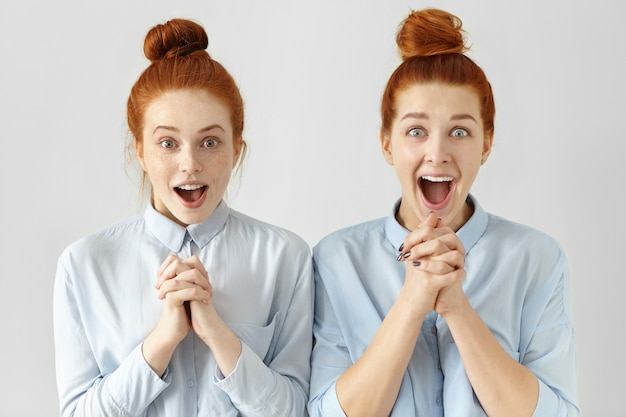 Twee mooie verraste werksters met rood haar, gekleed in dezelfde shirts