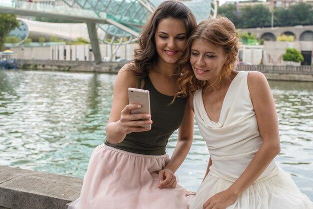 Twee mooie vriendin-vriendinnen zijn gefotografeerd, doen selfie, op een smartphone op de vredesbrug in tbilisi, georgië.