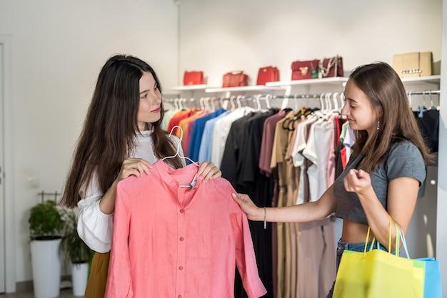Twee mooie vriendinnen kiezen een mooie rode jurk uit in een stijlvolle winkel