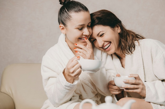 Twee mooie vriendinnen plezier gekleed in badjassen na spa procedures lachen terwijl een haar hoofd haar vriendin leunt.