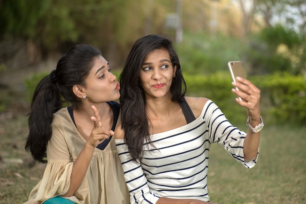 Twee mooie vriendinnen selfie met smartphone buitenshuis.