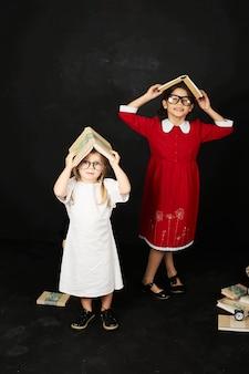 Twee mooie vriendinnen van schoolmeisjes die zich in de buurt van een schoolbord met boeken