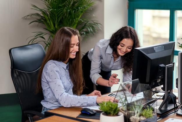 Twee mooie vrouwelijke architecten die met progect op modern kantoor werken.