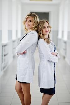 Twee mooie vrouwelijke artsen of medische arbeiders in witte jassen die in het ziekenhuis stellen.