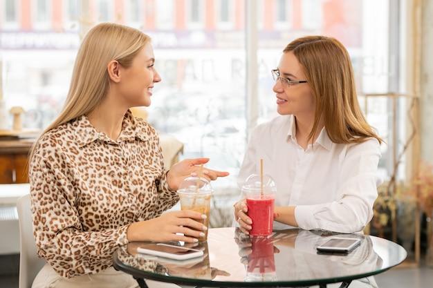 Twee mooie vrouwelijke shoppers zitten aan tafel in café terwijl ze smoothie hebben en bespreken wat ze willen kopen in het winkelcentrum