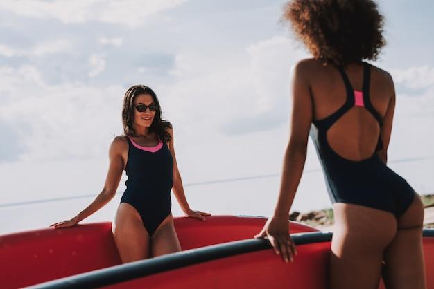 Twee mooie vrouwelijke surfers die zich op strand in zwempakken bevinden.