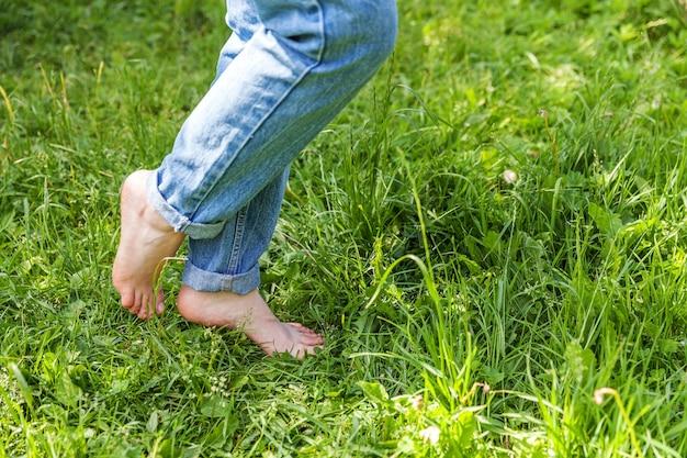Twee mooie vrouwelijke voeten lopen op gras in zonnige zomerochtend