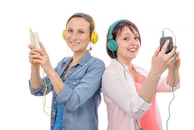 Twee mooie vrouwen die aan muziek met telefoon luisteren