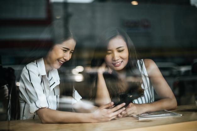 Twee mooie vrouwen die alles samen spreken bij de koffie van de koffiewinkel