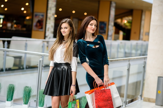 Twee mooie vrouwen die bij de wandelgalerij winkelen
