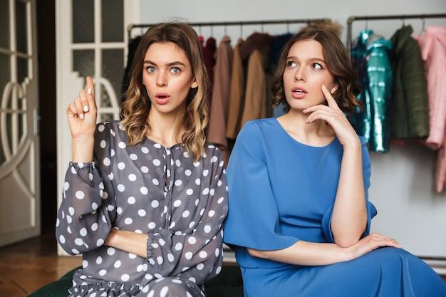 Twee mooie vrouwen die binnen in winkeltoonzaal zitten