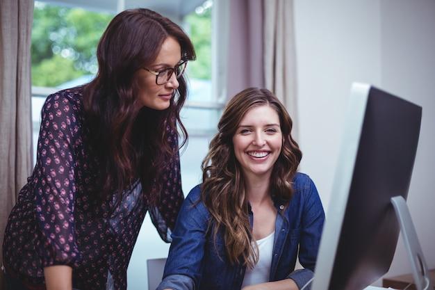 Twee mooie vrouwen die computer met behulp van