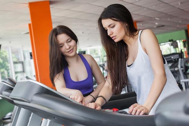 Twee mooie vrouwen die de tredmolen in de gymnastiek binnen proberen aan te zetten. mooie meisjes trainen in de sportschool. een groep fitness begginers die probeert te trainen