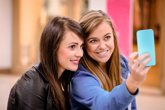 Twee mooie vrouwen die een selfie in winkelcomplex nemen