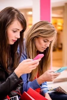 Twee mooie vrouwen die hun telefoon gebruiken